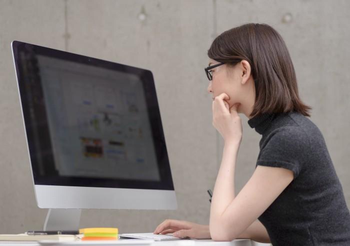 デスクトップパソコンでデスクワーク中の女性