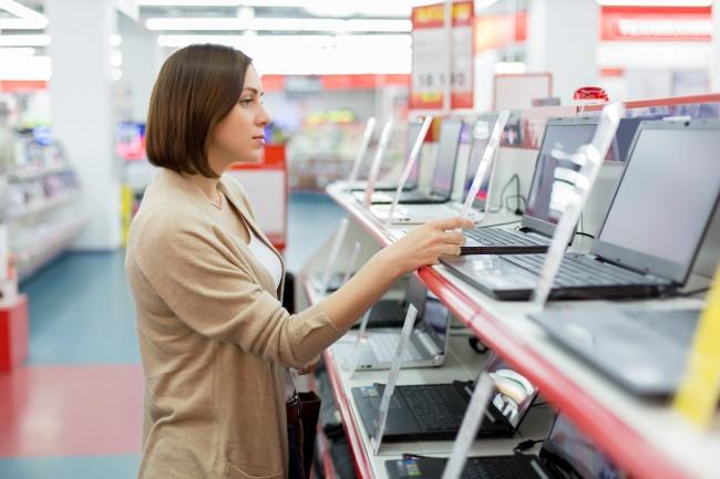 家電量販店でパソコンを選ぶ女性
