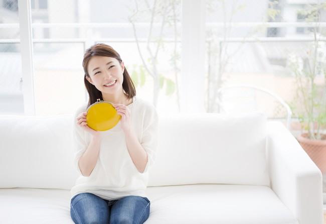 笑顔で財布を持つ女性