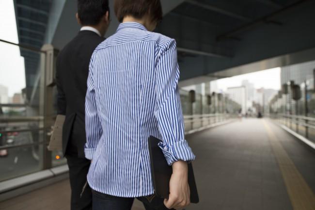 モバイルパソコンを片手に仕事場へ向かう女性