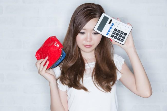 電卓と財布を持って困る女性
