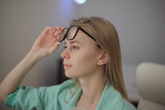 メガネをかけようとしている女性