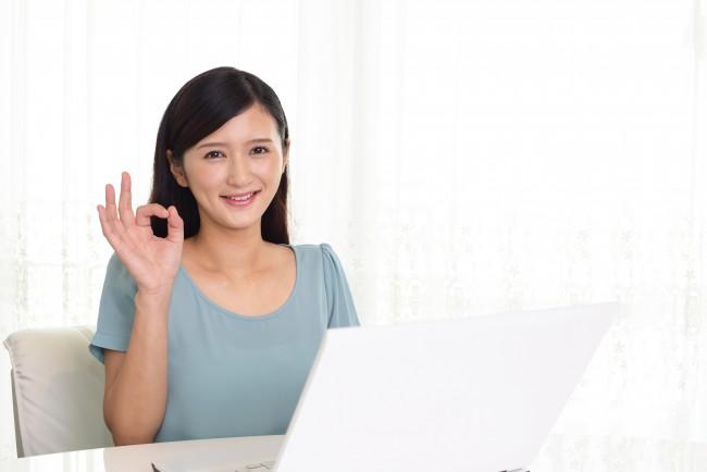 パソコンを見ながらOKサインを出す女性